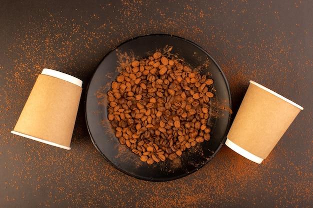 茶色のテーブルに空のカップと黒いプレート内のトップビューブラウンコーヒー種子