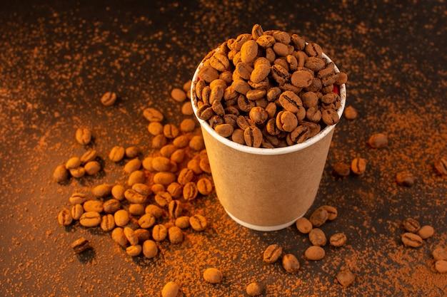 茶色のテーブルの上のプラスチック製のコップの中の上面の茶色のコーヒー種子