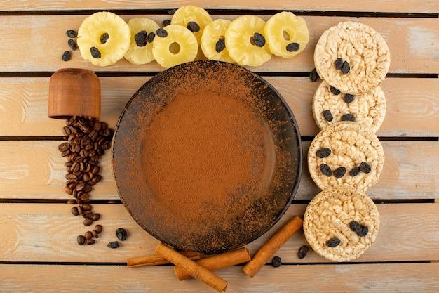 乾燥したパイナップルシナモンとクリームの素朴なテーブルコーヒーシードドリンク写真穀物のクラッカーと黒いプレート内のトップビューブラウンパウダーコーヒー