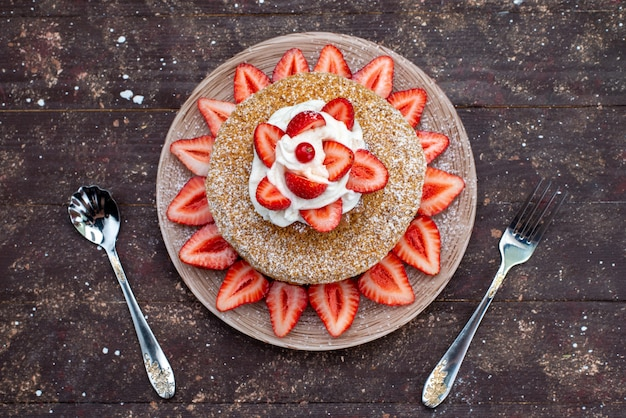 Кусочек торта с кремом и свежей красной клубникой внутри тарелки на темном фоне, вид сверху