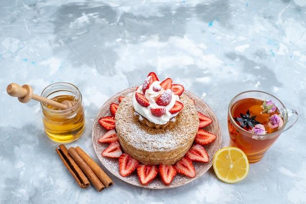 青灰色の背景にお茶とプレートの内側のクリームの新鮮な赤いイチゴの平面図ケーキスライス