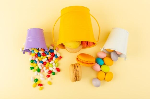 Вид сверху вкусные и сладкие конфеты и макароны на желтом столе