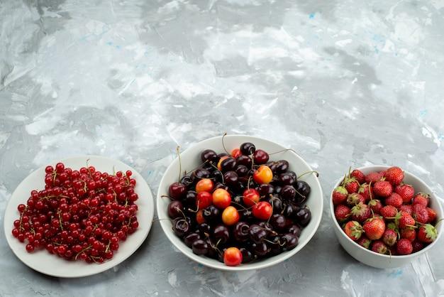 Вид сверху вишни и клубники с клюквой внутри ягод белой тарелки