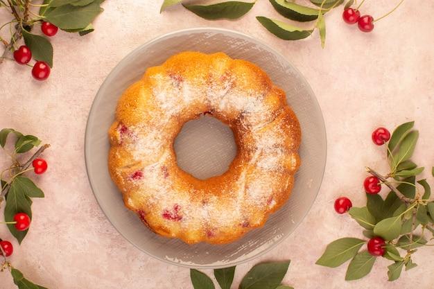 ピンクのデスクケーキビスケット砂糖菓子の灰色のプレートの内側に形成された上面のチェリーケーキ