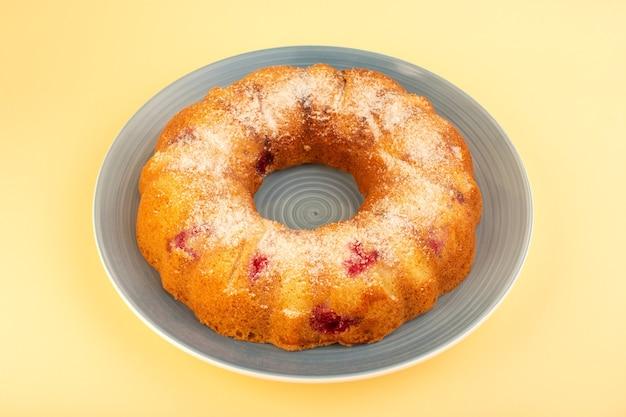 Круглый вишневый торт, вид сверху, сформированный внутри серой тарелки на желтом письменном столе, печенье, сахар, сладкое