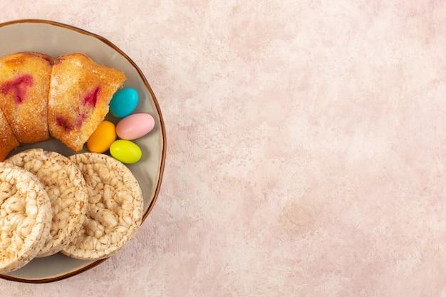 Вид сверху на кусочки вишневого торта с конфетами и печеньем на розовом настольном кексе