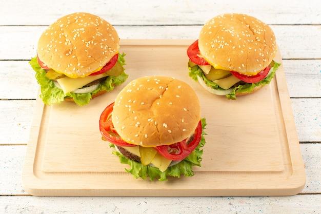 木製の机の上のチーズとグリーンサラダとトップビューチキンハンバーガー