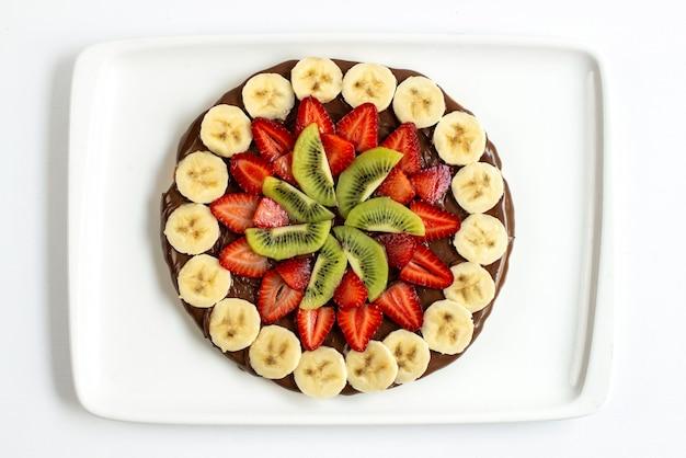 Шоколадный торт с нарезанной клубникой, бананами и киви, вид сверху, оформленный внутри белой тарелки на белом фоне, сладкое празднование дня рождения