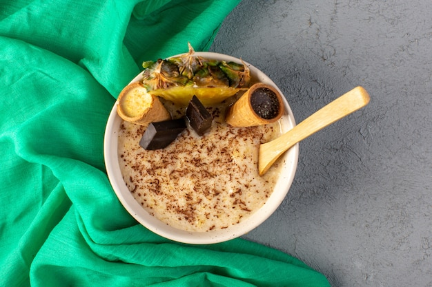 Вид сверху шоколадный десерт коричневого цвета с ломтиками ананаса шоколадные батончики внутри белой тарелки вместе с зелеными салфетками на сером