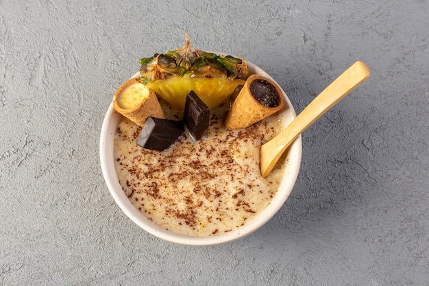 Вид сверху шоколадный десерт коричневый с ломтиком ананаса шоколадные батончики внутри белой тарелке на сером