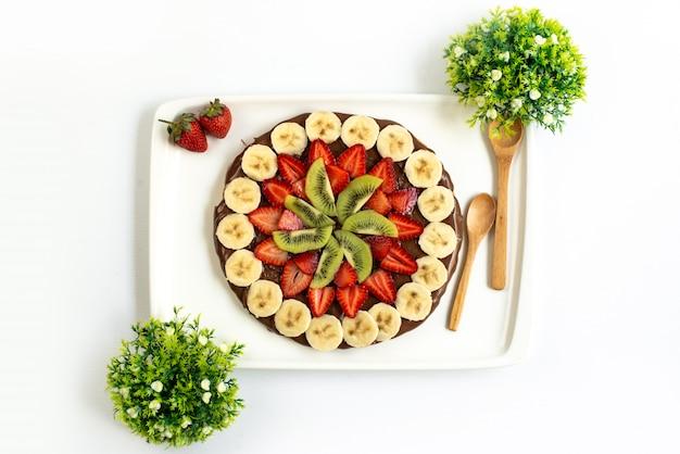 Вид сверху шоколадно-клубничный десерт вкусные сладкие украшенные свежие бананы и киви вместе с растениями, разбросанными по всему белому фону, фруктовый торт экзотический