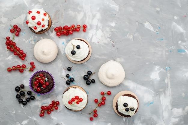 白い背景の上のケーキビスケットドーナツチョコレートのフルーツで設計されたドーナツクリームとトップビューチョコレートケーキ