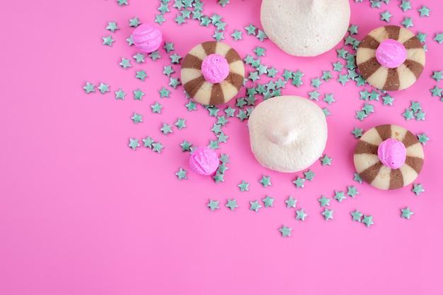 トップビューチョコレートクッキーとピンクの机のメレンゲ、クッキービスケット砂糖菓子