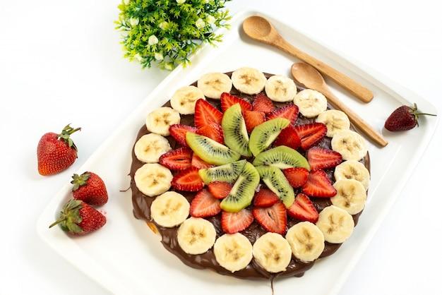 Шоколадно-фруктовый торт, вид сверху, вкусный с нарезанными фруктами, клубникой и деревянными ложками внутри белого настольного печенья с сахаром