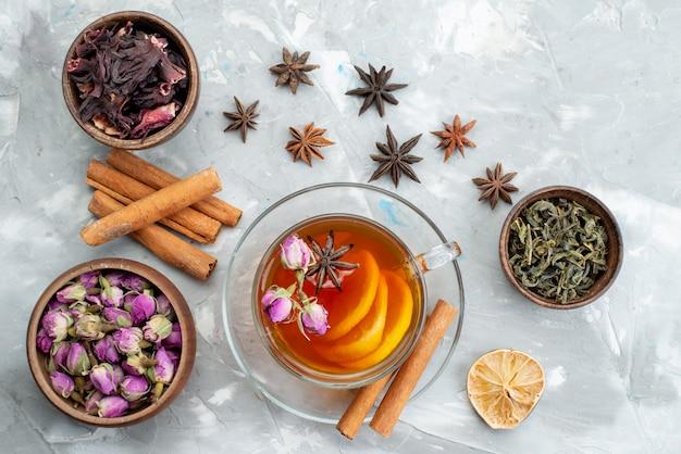 Вид сверху корицы и цветов вместе с долькой сушеного лимона и чашкой чая на светлом столе с сухофруктами.