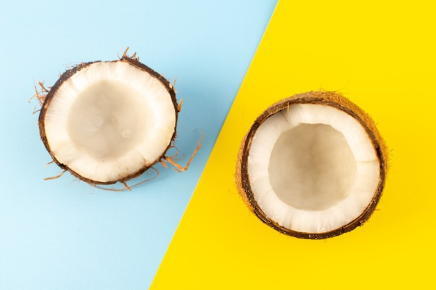 Вид сверху на кокосовые орехи, нарезанные ломтиками, и свежая цельная молочная свежая мякоть, изолированная на голубом и желтом льду