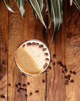 Кофейный коктейль, вид сверху, со свежими коричневыми кофейными семечками на коричневом деревянном столе, пить кофе из семян