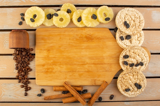 Вид сверху кофейные зерна с сушеным ананасом, корицей и сухариками на сливках деревенский стол кофейный напиток фото зерно гранулы