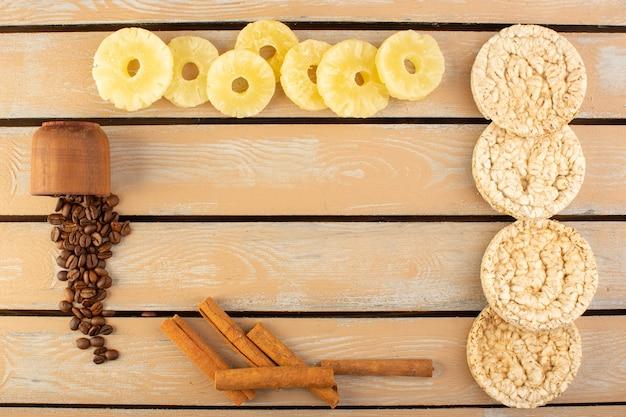 Вид сверху кофейных зерен с сушеными ананасами, корицей и сухариками на сливочном деревенском столе кофейных зерен напиток фото зерна