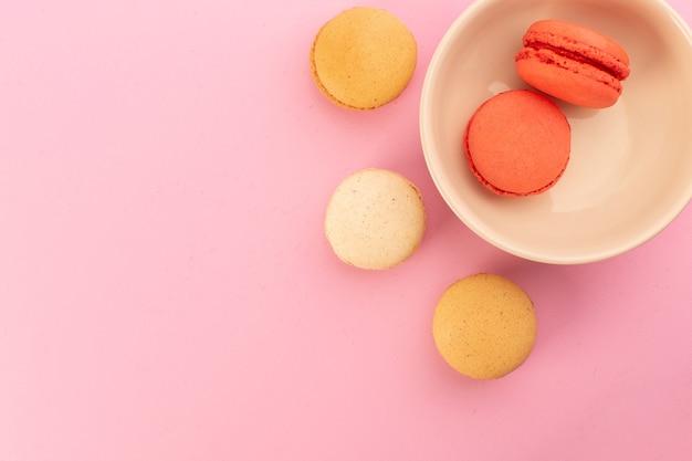 Цветные французские макароны, вид сверху, вкусные и запеченные на розовом столе, бисквит, сладкий сахар