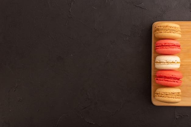 Цветные французские макароны, вид сверху, вкусные на деревянном столе, и темный стол, торт, бисквит, сахарная конфета, сладкий