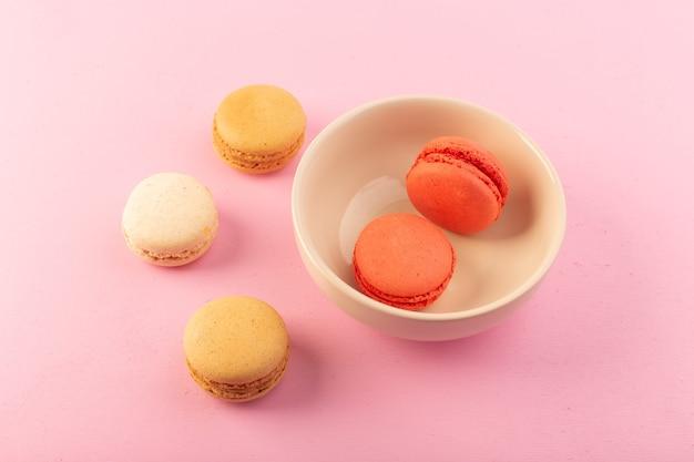 Вид сверху цветные французские макароны внутри и снаружи тарелки на розовом столе