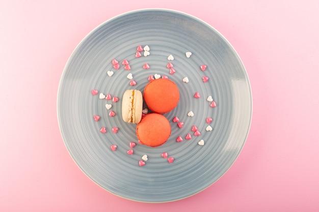 Вид сверху цветные французские макароны внутри синей тарелки