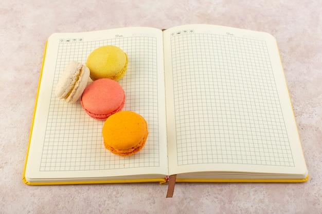 Цветные французские макароны на тетради и розовый настольный торт, сахарное сладкое печенье, вид сверху