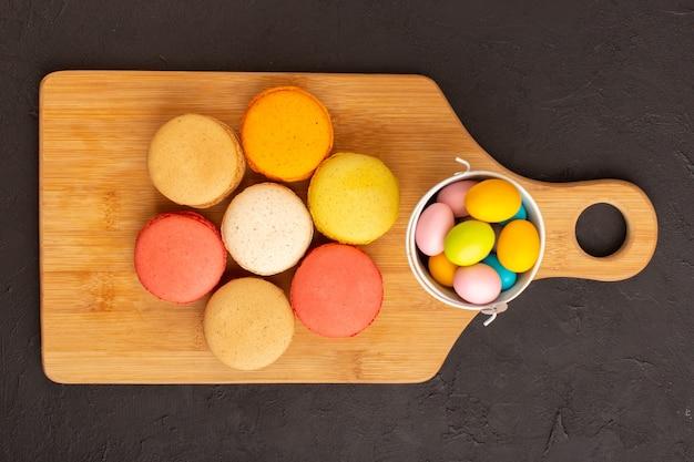 Цветные французские макароны с красочными конфетами, вид сверху