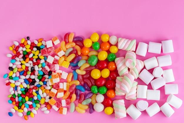 분홍색 책상에 다른 색깔의 달콤하고 맛있는 사탕의 상위 뷰 다채로운 사탕 구성