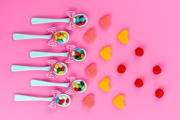 ピンクの机の上の色のマーマレード、甘い砂糖の虹と一緒に緑のスプーンの中にあるカラフルなキャンディーのトップビュー