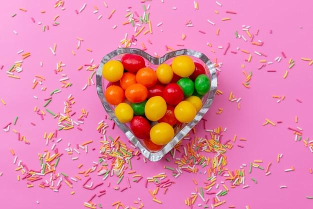 ピンクの机の上のハート型のプレートの中のトップビューカラフルなキャンディー、色の虹砂糖甘い