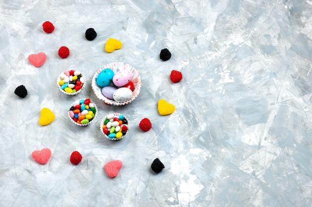 Вид сверху красочные конфеты внутри маленьких тарелок вместе с мармеладными конфетами в форме сердца на серо-белом фоне.
