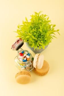Вид сверху красочные конфеты с французскими макаронами и растениями