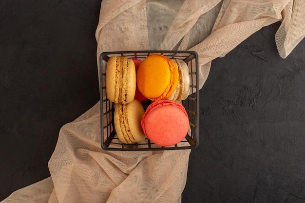Вид сверху красочные французские макароны вкусные и запеченные внутри корзины на темном столе, торт, печенье, печенье, сахар