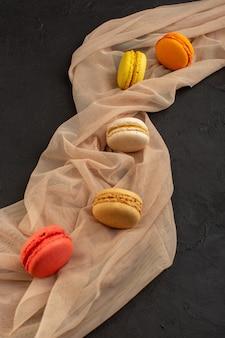 Вид сверху красочные французские макароны вкусные и запеченные на темном столе торт печенье печенье сахар