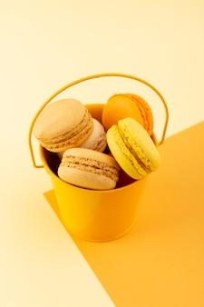 黄色のデスクケーキビスケットシュガースイートの黄色いバケツの内側でおいしいカラフルなフランスのマカロンのトップビュー