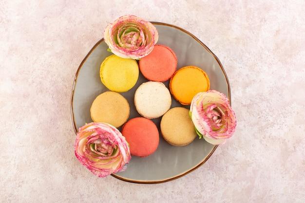 ピンクのデスクシュガーケーキビスケット甘い上おいしいプレート内部カラフルなフランスのマカロンのトップビュー