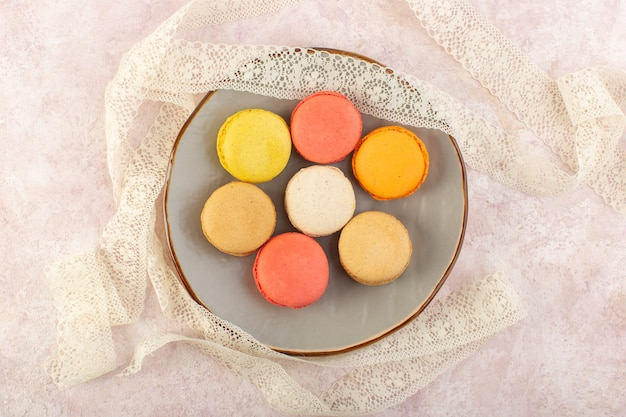ピンクのデスクケーキビスケットシュガーカラーの丸皿の中のトップビューカラフルなフランスのマカロン