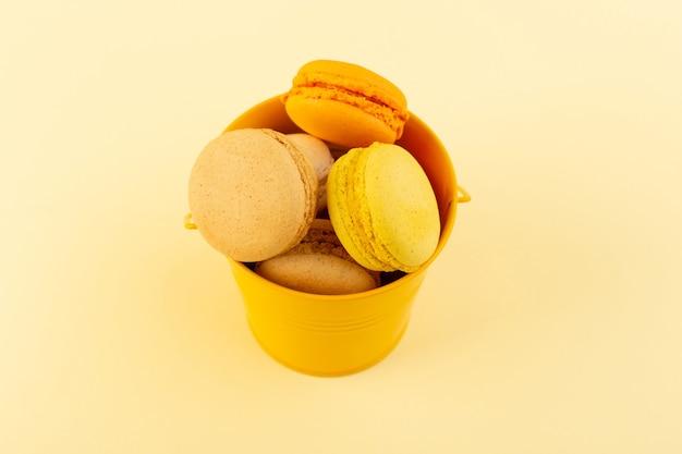 Вид сверху красочные французские макароны внутри желтой корзины