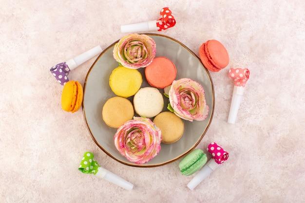 Вид сверху красочные французские макароны на розовом столе сахарный торт бисквитный сладкий
