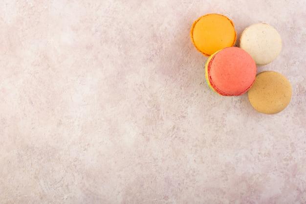 Вид сверху красочные французские макароны круглой формы и вкусные на розовом столе, торт, бисквитный сахар