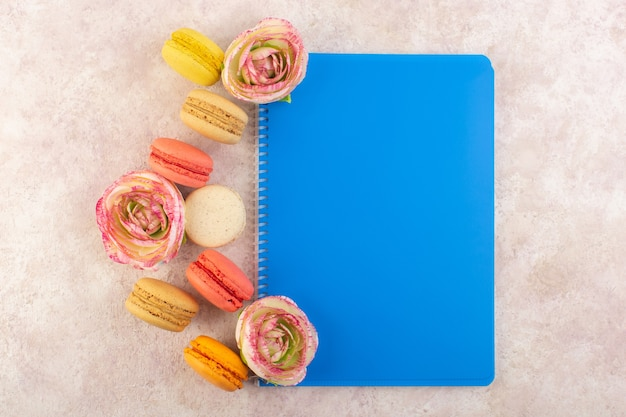 Вид сверху красочные французские макароны круглой формы и вкусные с цветами и тетрадью на розовом столе, торт, печенье, сладкое