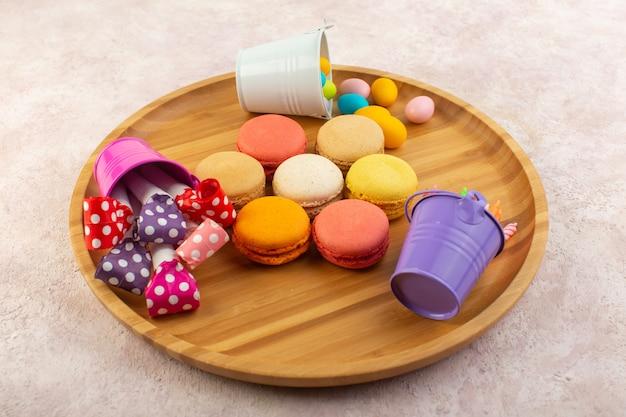 Вид сверху красочные французские макароны круглой формы и вкусные на розовом столе, торт, бисквит, сладкий
