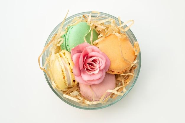 Вид сверху красочные французские макароны круглые, образованные восхитительно внутри круглого стекла на белом, цвет бисквитного торта