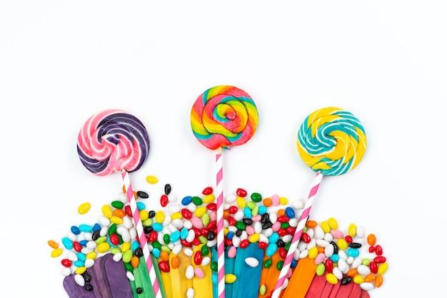 Вид сверху красочные леденцы на палочке вместе с конфетами на белом, цветном радужном сахаре
