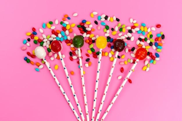 Вид сверху красочные леденцы на палочке вместе с цветными конфетами на розовом, цветном сладком сахаре