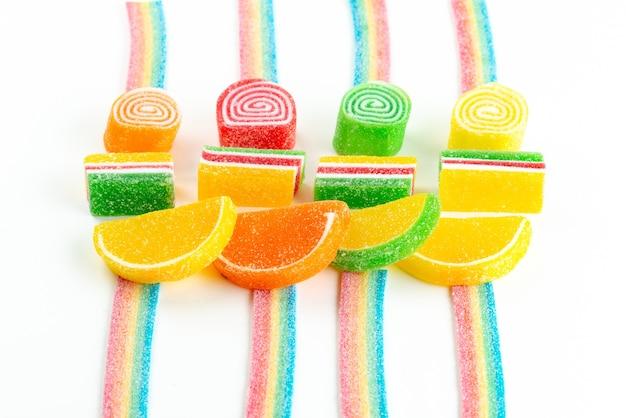 Красочный мармелад, вид сверху, представляет собой липкие и восхитительные кондитерские изделия, выложенные белым, цветным сахаром.