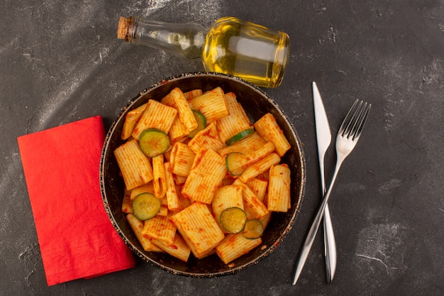 Вид сверху приготовленная итальянская паста с томатным соусом и огурцом внутри сковороды