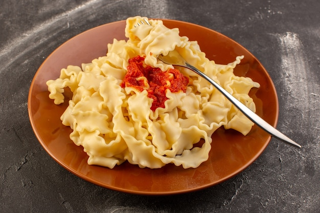 Вид сверху приготовленные итальянские макароны с томатным соусом внутри коричневой тарелки